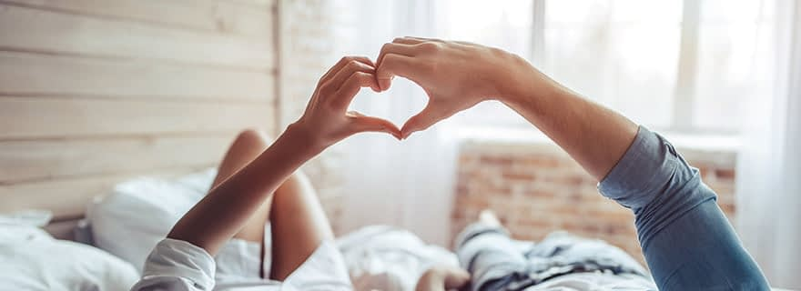 Men and Womam in the bed making love heart together
